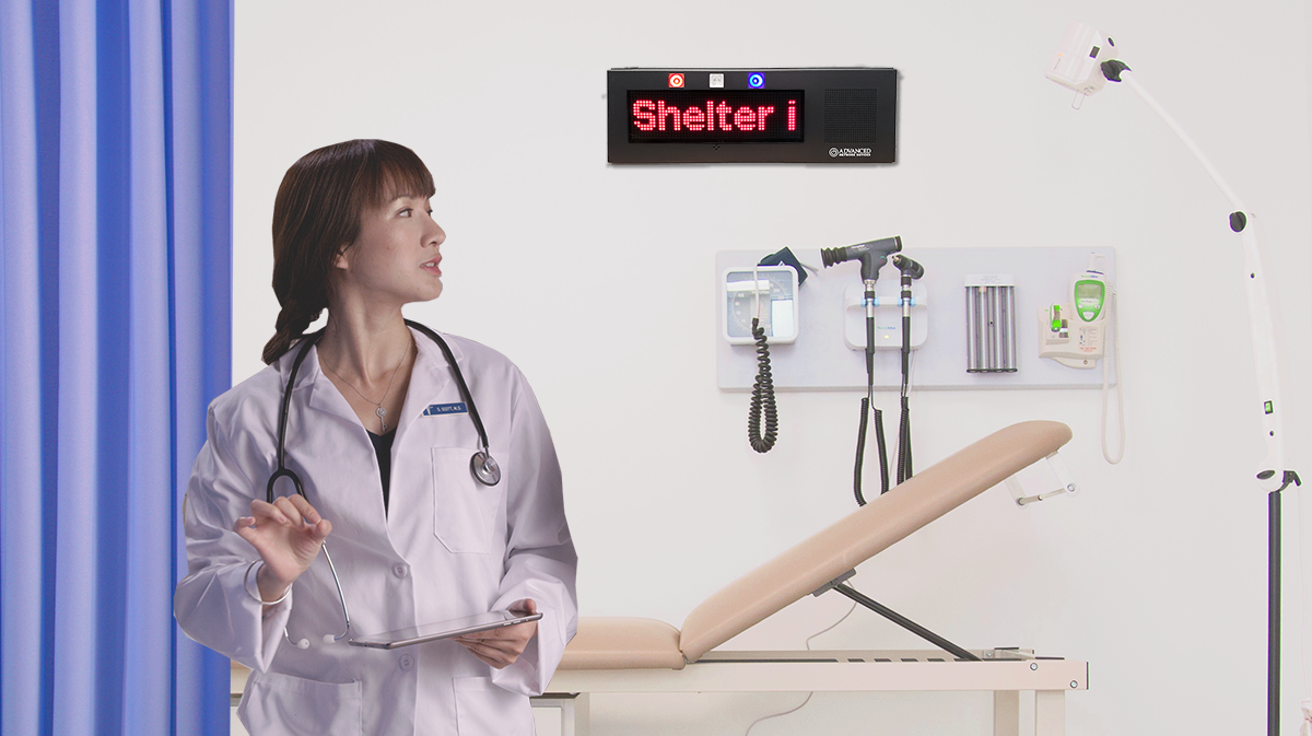 An IP display device shows a shelter in place message in a healthcare exam room.