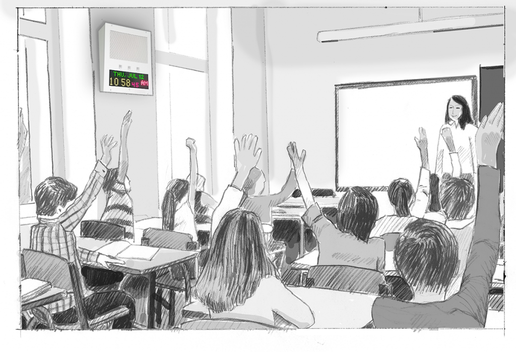 A teacher with elementary students in a classroom. An IP Speaker with Display on the wall shows the time.