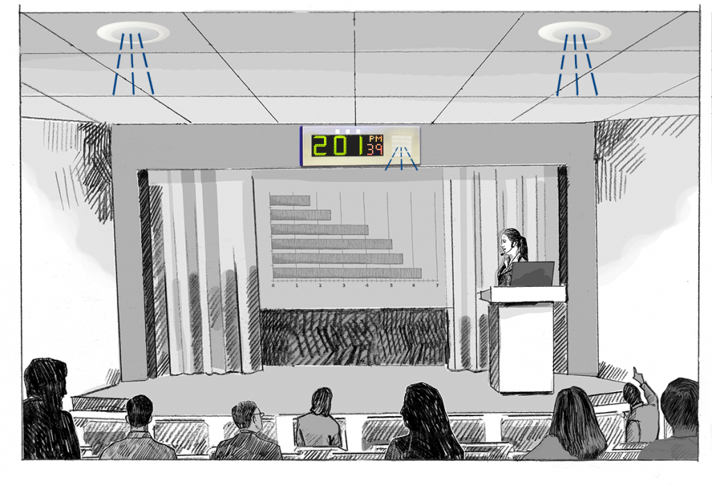 A woman with a headset microphone presents a bar chart in a lecture hall, while IP devices amplify her voice.